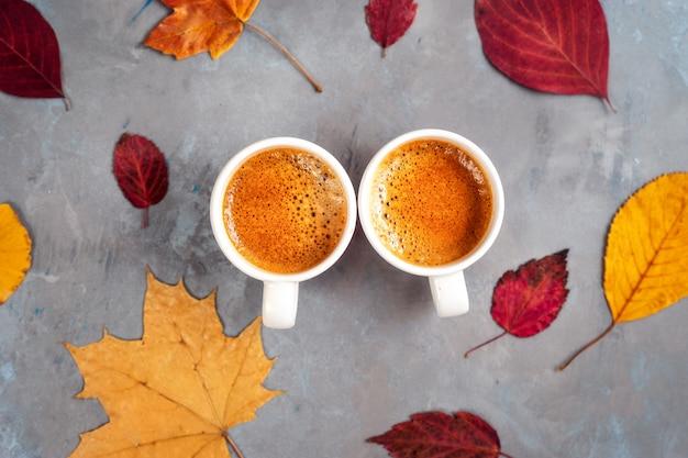 Vista dall'alto di due tazze di caffè intorno alle foglie gialle