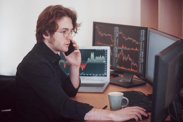 Vista dall'alto di e broker di trading online mentre si accettano ordini per telefono. schermi computer multipli pieni di grafici e analisi dei dati