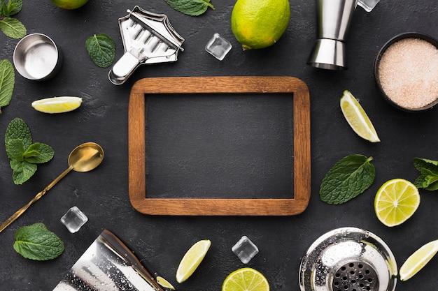 Vista dall'alto di elementi essenziali cocktail con lavagna e lime