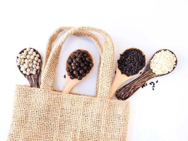 Vista dall'alto di erbe di cereali in un cucchiaio di legno con semi di pepe bianco, pepe nero, sesamo nero e sesamo bianco in sacchetto di tela