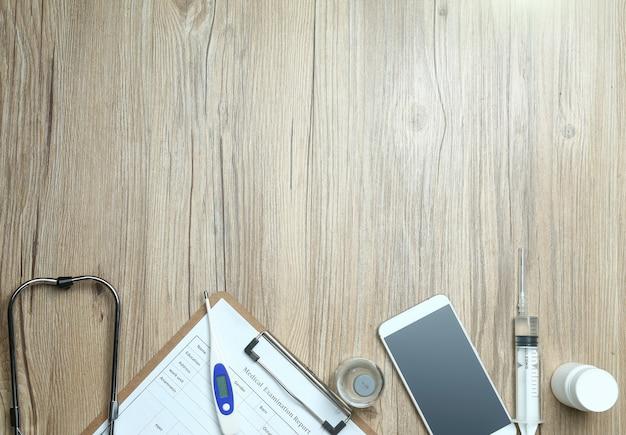 Vista dall'alto di esame di esame medico, cellulare e attrezzature mediche sulla scrivania in legno