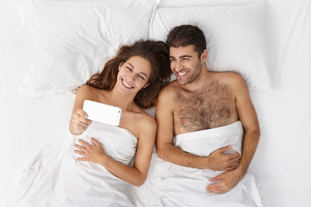 Vista dall'alto di felice giovane coppia europea sdraiata a letto su lino bianco e prendendo selfie sul cellulare