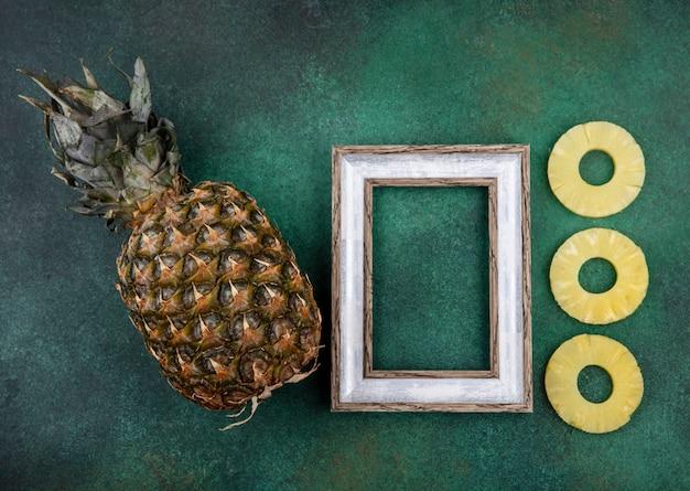 Vista dall'alto di fette di ananas e ananas con cornice sulla superficie verde