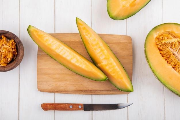 Vista dall'alto di fette di melone cantalupo fresche e deliziose sul bordo di cucina in legno con coltello su legno bianco