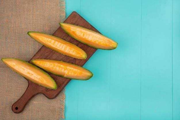 Vista dall'alto di fette di melone cantalupo fresche e deliziose sulla tavola di cucina in legno sul panno del sacco sul blu con lo spazio della copia