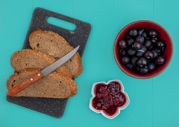 Vista dall'alto di fette di pannocchia marrone seminate con coltello sul tagliere e marmellata di lamponi con bacche di prugnole su sfondo blu