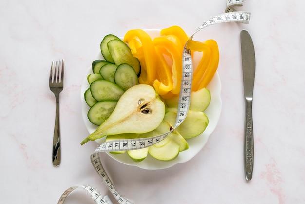 Vista dall'alto di fette organiche di verdure e frutta sul piatto con nastro adesivo di misurazione