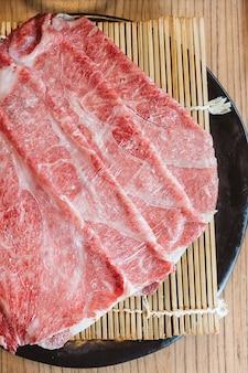 Vista dall'alto di fette rari wagyu a5 manzo su stuoia di bambù con piastra nera per bollire in zuppa shabu.