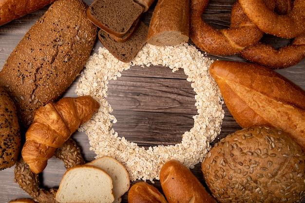 Vista dall'alto di fiocchi d'avena impostato in forma circolare e pane intorno come baguette di segale bianco baguette pannocchia su fondo in legno con spazio di copia