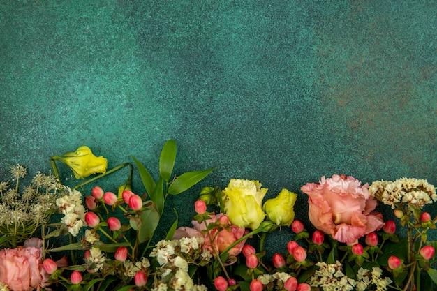 Vista dall'alto di fiori belli e freschi con foglie su gre con spazio di copia