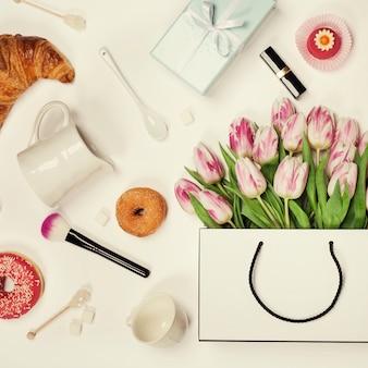 Vista dall'alto di fiori primaverili, caffè, cornetti, confezione regalo, trucco