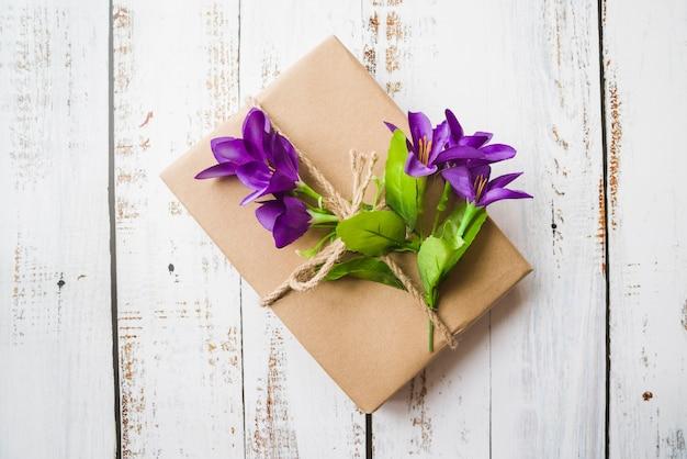 Vista dall'alto di fiori viola legati con confezione regalo sul contesto in legno bianco