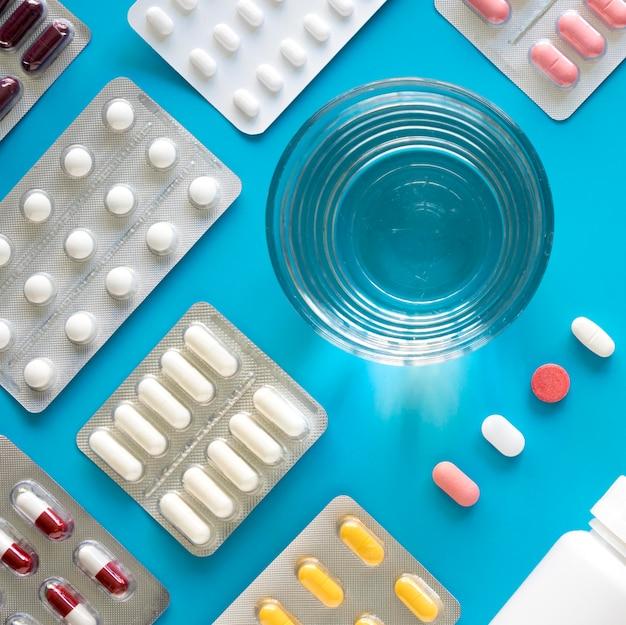 Vista dall'alto di fogli di pillola con un bicchiere d'acqua