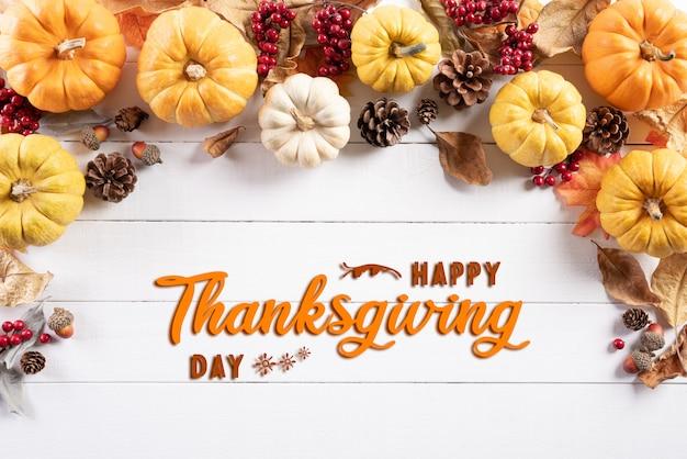 Vista dall'alto di foglie di acero autunno con zucca e bacche rosse. concetto di giorno del ringraziamento.