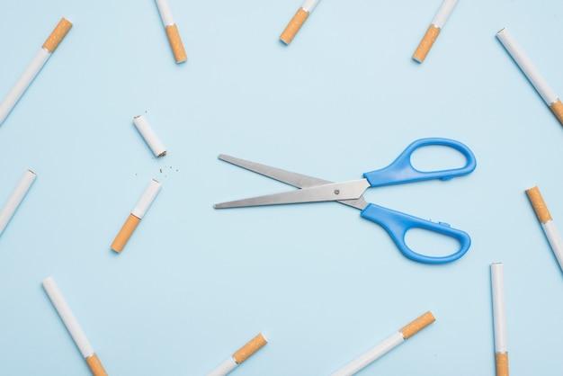 Vista dall'alto di forbice e sigaretta rotto sulla superficie blu