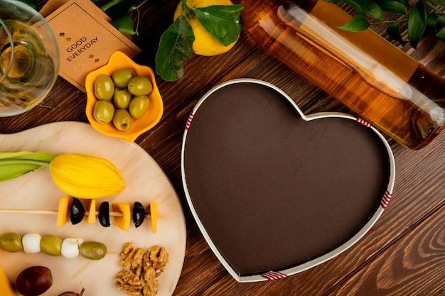 Vista dall'alto di formaggio impostato come cheddar e parmigiano con uva di noce di oliva e fiori sul tagliere con scatola a forma di cuore vino bianco limone e buona carta di tutti i giorni su fondo in legno