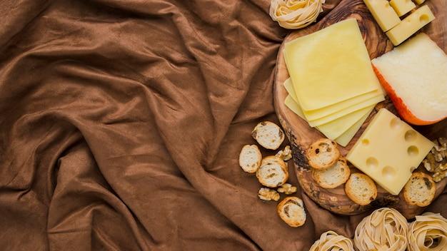 Vista dall'alto di formaggio, pasta e pane su tessuto frantumato