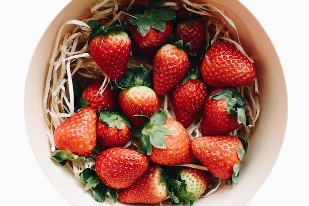 Vista dall'alto di fragole fresche in una scatola di legno rotonda
