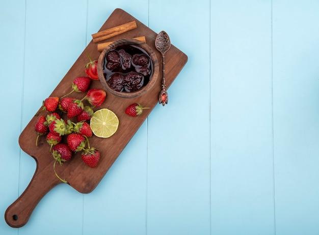 Vista dall'alto di fragole fresche su una tavola di cucina in legno con marmellata di fragole con una fetta di lime su sfondo blu con spazio di copia