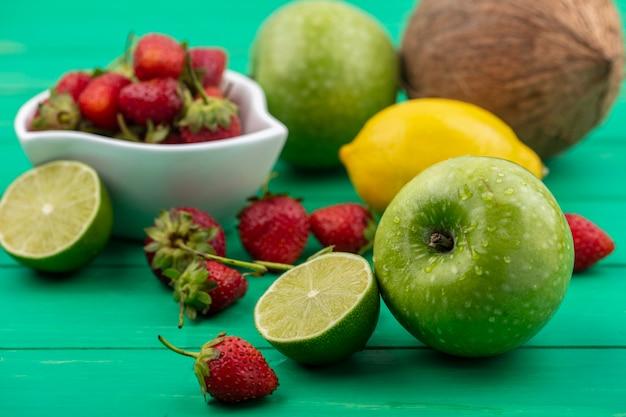 Vista dall'alto di fragole su una ciotola con frutta fresca come mele, limone e cocco isolato su uno sfondo verde