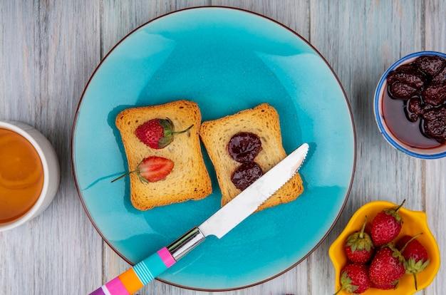 Vista dall'alto di fragole sul pane su un piatto blu con coltello con marmellata di fragole su una ciotola con fragole fresche su uno sfondo di legno grigio