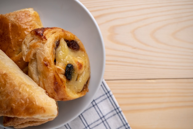 Vista dall'alto di freschi panini dolci e torta collocato su un vassoio in legno e tovagliolo per la colazione del mattino.