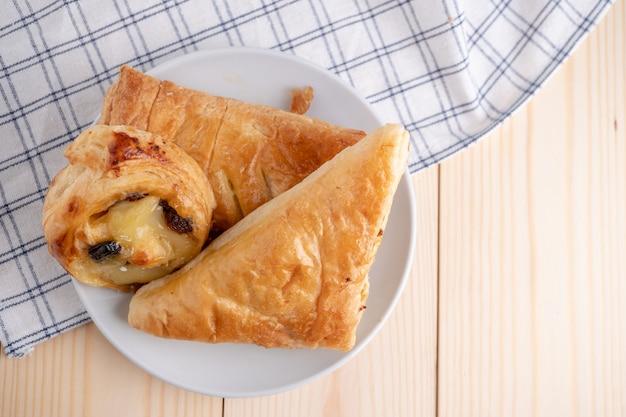 Vista dall'alto di freschi panini dolci e torta collocato su un vassoio in legno e tovagliolo per la colazione del mattino