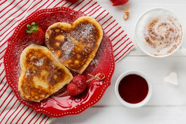 Vista dall'alto di frittelle a forma di cuore con fragole