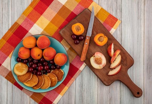 Vista dall'alto di frittelle con ciliegie e albicocche nel piatto e tagliare la pesca albicocca con il coltello sul tagliere sul panno plaid su fondo di legno