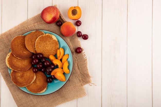 Vista dall'alto di frittelle con ciliegie e pezzi di albicocche nel piatto e ciliegie di albicocche su tela di sacco e su fondo di legno con spazio di copia