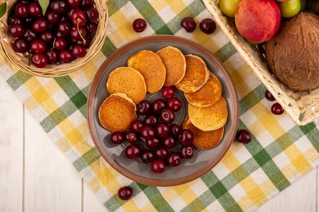 Vista dall'alto di frittelle con ciliegie nel piatto e cesto di ciliegie con cesto di albicocca noce di cocco prugna su panno plaid e sfondo di legno