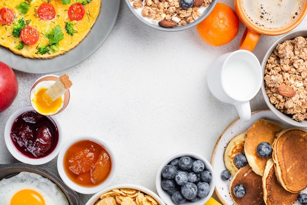 Vista dall'alto di frittelle e frittata con marmellata e mirtilli per la colazione