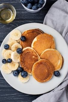 Vista dall'alto di frittelle per la colazione con mirtilli e miele
