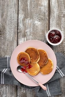 Vista dall'alto di frittelle sul piatto per la colazione con marmellata e cucchiaio