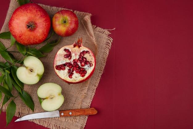 Vista dall'alto di frutta come mezza mela tagliata con uno intero e melograno intero con metà uno e coltello con foglie su tela di sacco sulla superficie rossa