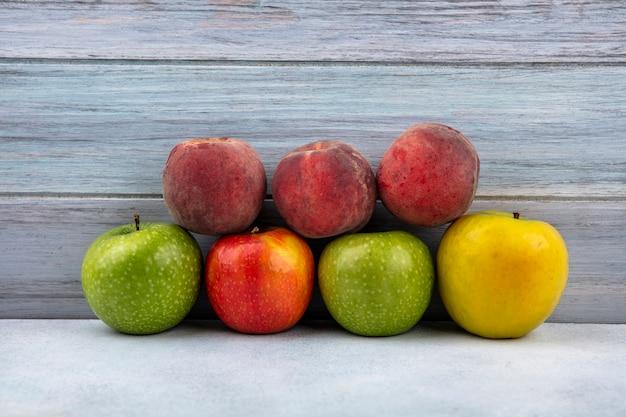 Vista dall'alto di frutta fresca come mele colorate e pesche su legno
