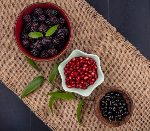 Vista dall'alto di frutti come melagrana mora e bacche di prugnola in ciotole con foglie su tela di sacco sulla superficie nera