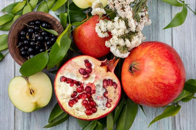 Vista dall'alto di frutti come melograno e metà di mela con quelli interi e ciotola di prugnolo con fiori e foglie sulla superficie nera