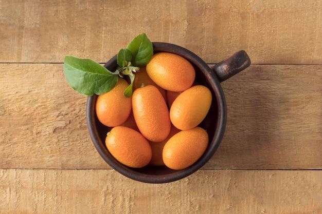 Vista dall'alto di frutti di kumquat in tazza di argilla su sfondo di legno