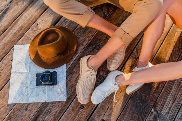 Vista dall'alto di gambe di coppia che viaggiano in estate vestite di scarpe da ginnastica