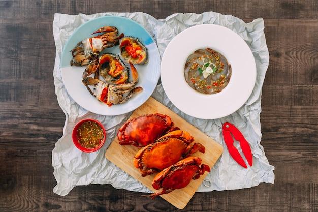 Vista dall'alto di gamberi crudi fermentati con salsa di pesce e granchio di mare con uova di granchio sott'aceto e granchi di fango gigante al vapore serviti con salsa di frutti di mare speziati in stile tailandese.