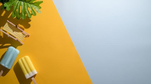 Vista dall'alto di ghiaccioli di banana e lampone blu su sfondo giallo e blu piatto disteso