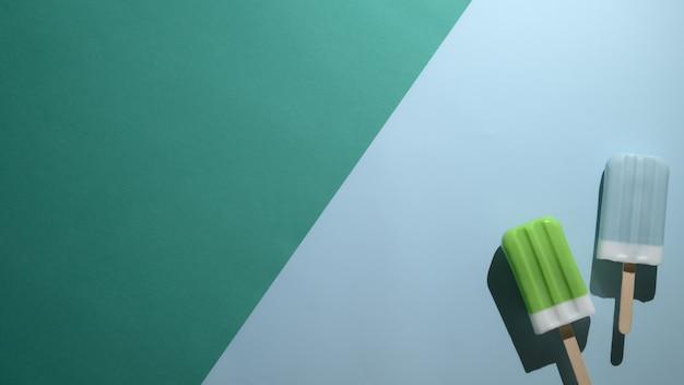 Vista dall'alto di ghiaccioli di lime e lampone blu su sfondo verde e blu piatto disteso