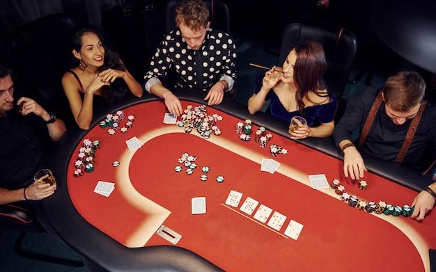 Vista dall'alto di giovani eleganti che giocano a poker nei casinò