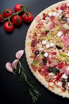 Vista dall'alto di guarnire gustosa pizza italiana sul piano di lavoro della cucina