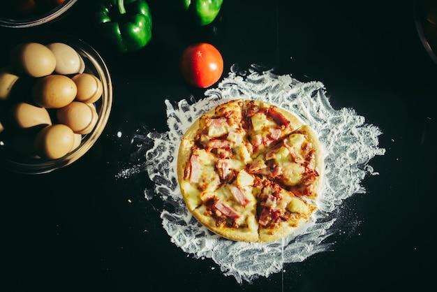 Vista dall'alto di gustosa pizza, formaggio e prosciutto su un tavolo di legno d'epoca.