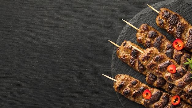 Vista dall'alto di gustosi kebab sulla piastra con copia spazio