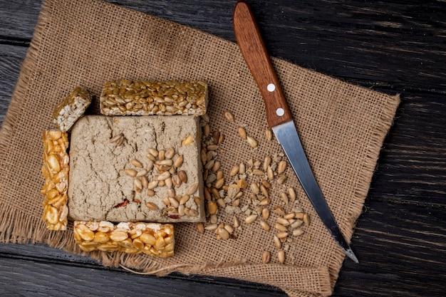 Vista dall'alto di halva gustoso con barrette di miele con arachidi e semi di girasole su tela di sacco