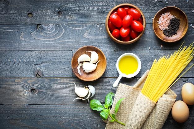 Vista dall'alto di ingredienti italiani per pomodoro e spaghetti basilici.