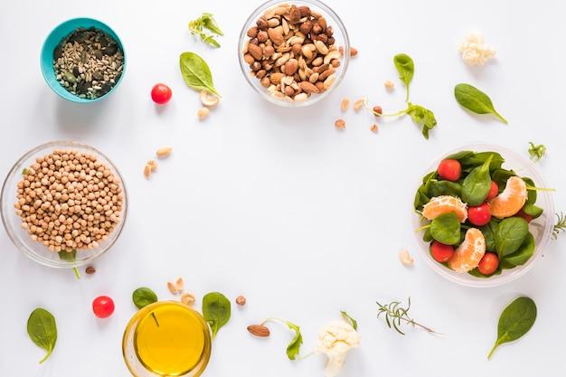 Vista dall'alto di ingredienti sani in ciotole su sfondo bianco con uno spazio vuoto per il testo